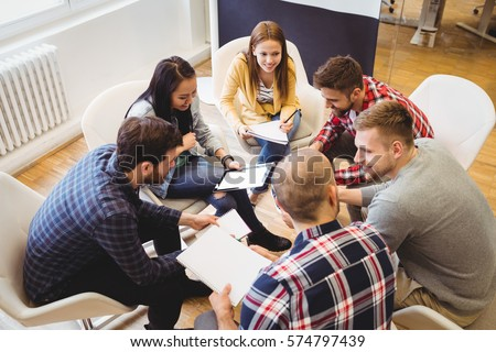 High angle view of business people discussing in meeting room at creative office against projector screen