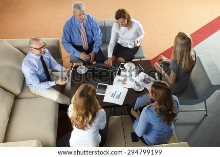 High angle view of business team in a meeting. Businesswomen and businessmen sitting around conference table and working with laptop and digital tablet while consulting.  #294799199