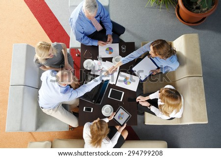 High angle view of business team sitting around the desk and shaking hands. Businesswomen and businessmen working with laptop and digital tablet while making business deal.
