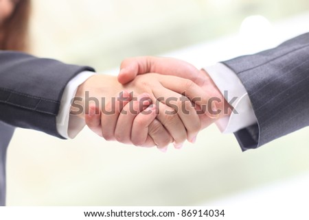 High angle view of business woman and man shaking hands