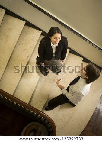 High angle view of businessman talking to businesswoman on stairway
