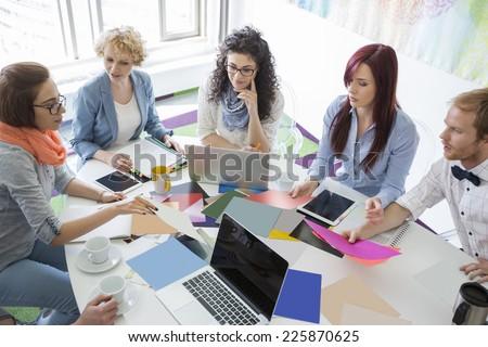 High angle view of businesspeople analyzing photographs in creative office