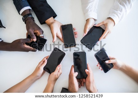 High Angle View Of Businesspeople Hand Using Mobile Phone