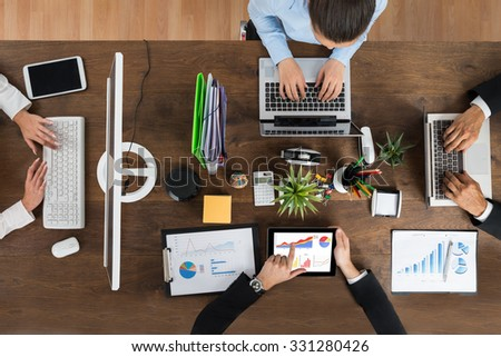 High Angle View Of Businesspeople Working On Electronic Devices At Wooden Desk