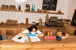 High angle view of cafe owner in medical mask at table with smartphone, papers, calculator, card with quarantine lettering, payment terminal and fruits