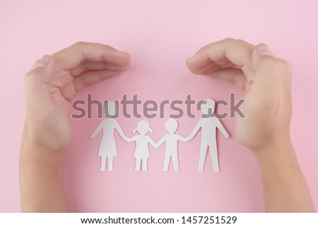 High Angle View Of Child Hand Protecting Family Papercut On pink background