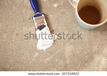 High angle view of coffee mug and paintbrush on floor