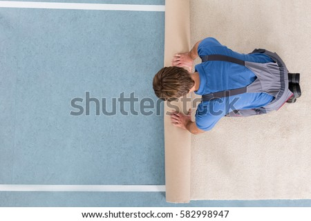 High Angle View Of Craftsman In Overalls Unrolling Carpet On Floor