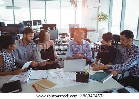 High angle view of creative business colleagues discussing around desk in office