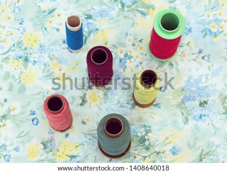 high angle view of different spools on floral background #1408640018