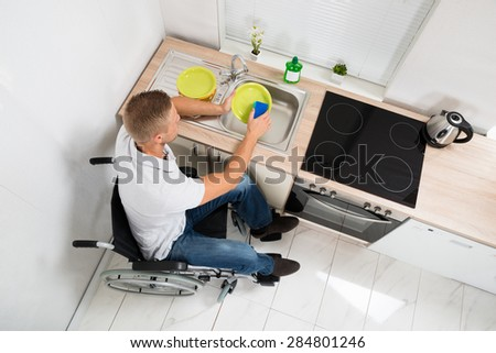 High Angle View Of Disabled Man On Wheelchair With Sponge Washing Dishes