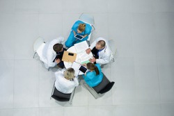 High angle view of doctors and surgeons interacting with each other in meeting at hospital