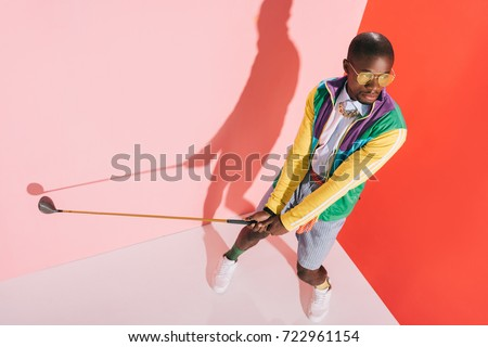 high angle view of fashionable african american man in sunglasses playing golf in studio #722961154