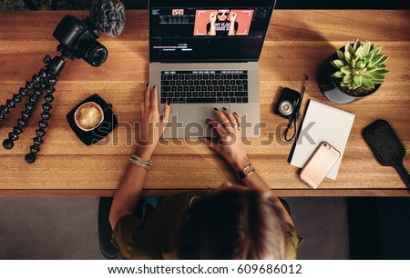 High angle view of female vlogger editing video on laptop. Young woman working on computer with cameras and accessories on table.