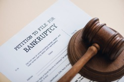 High angle view of gavel on document with petition to file for bankruptcy lettering isolated on beige