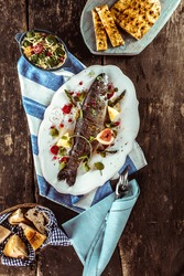 High Angle View of Grilled and Garnished Whole Fish on Wooden Table Surrounded by Other Dishes and Linen Napkins