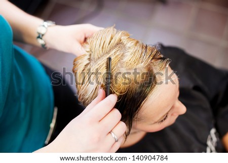 High angle view of hair dresser combing client\'s hair in salon