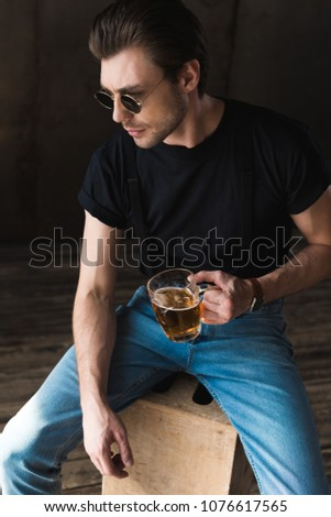 high angle view of handsome young man in black t-shirt and sunglasses holding mug of beer #1076617565