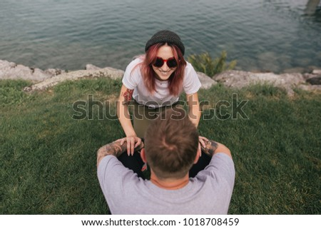 high angle view of happy young couple looking at each other while sitting on green grass near lake #1018708459