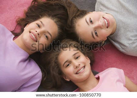 High angle view of Hispanic sisters laying on floor