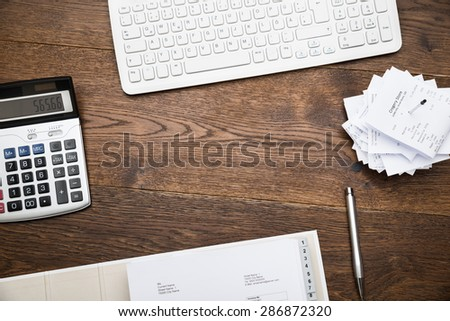 High Angle View Of Keyboard And Calculator With Receipts On Desk