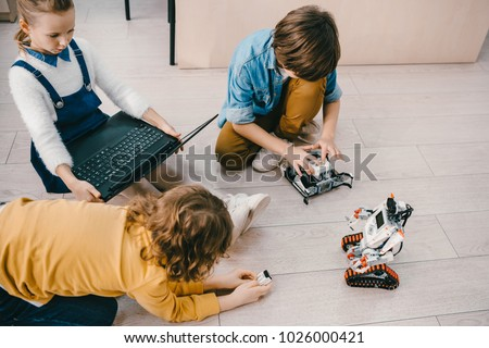 high angle view of kids sitting on floor at stem education class with robots and laptop #1026000421