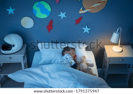 High angle view of little boy dreaming of becoming an astronaut while sleeping with teddy bear in space decorated room. Top view of dreamer child sleeping on bed during the night and the light on.