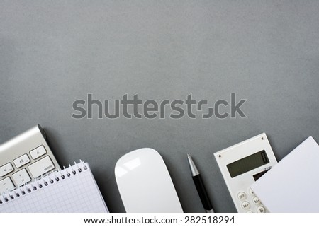 High Angle View of Mac Computer Keyboard and Mouse with Note Pads, Calculator and Pen on Grey Desk with Ample Copy Space