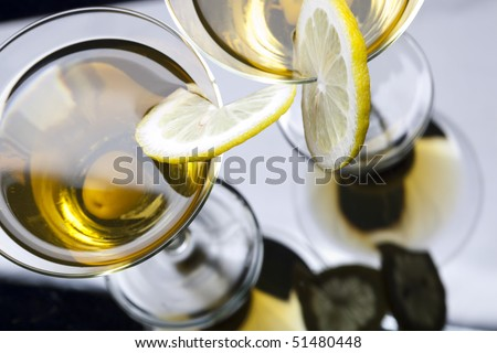 High angle view of martini with olives isolated on black focus on rim of glass and lemon slice. Shallow depth of field. High  view