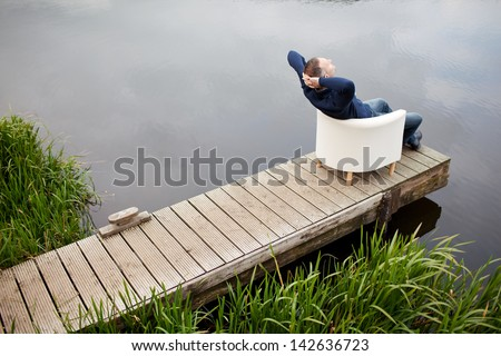 High angle view of mature man with hands behind head relaxing on chair at pier