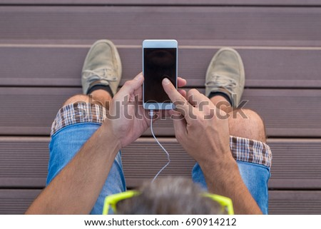 High angle view of modern urban man using blank screen smart phone against wooden floor #690914212