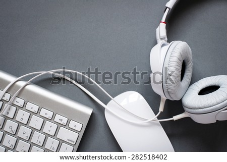 High Angle View of Modern White Audio Headphones with Cord, Mac Computer Keyboard and Mouse on Grey Desk Background with Copy Space