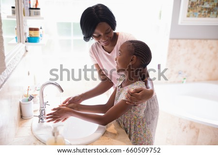 High angle view of mother and daughter washing hands at sink in bathroom, Coronavirus hand washing for clean hands hygiene Covid19 spread prevention.