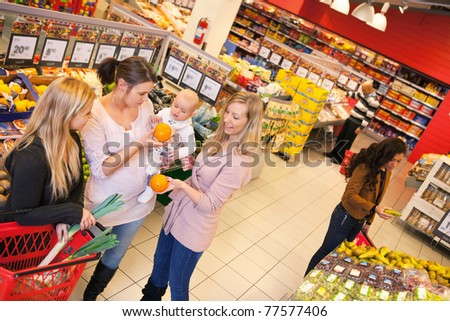 High angle view of mother carrying child with friends shopping in supermarket