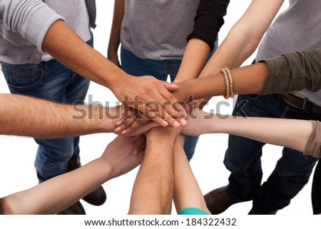 High angle view of multiethnic college students stacking hands against white background
