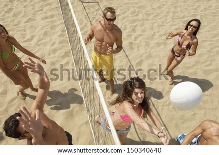 High angle view of multiethnic friends playing volleyball on beach