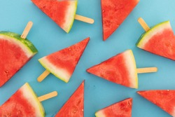 High angle view of multiple watermelon triangles on wooden sticks on blue background. fresh fruit healthy food concept.