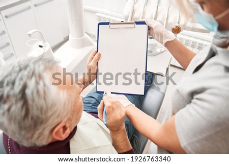High angle view of multiracial woman stomatologist having conversation with her male patient and filing documents while sitting at the dentistry room. People, medicine, stomatology and health care Foto stock ©