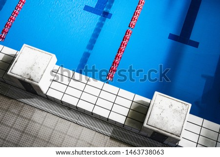 High angle view of olympic size swimming pool with starting platforms and lane rope high angle view no people