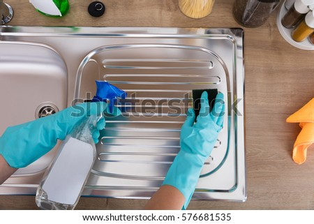 High Angle View Of Person Hands Cleaning Kitchen Sink With Spray Bottle And Sponge #576681535