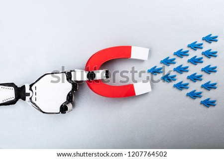 High Angle View Of Robot Attracting Human Figures With Horseshoe Magnet On Grey Background #1207764502