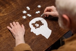 high angle view of senior man collecting jigsaw puzzle as dementia rehab