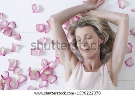 High angle view of senior woman laying on floor with flower petals