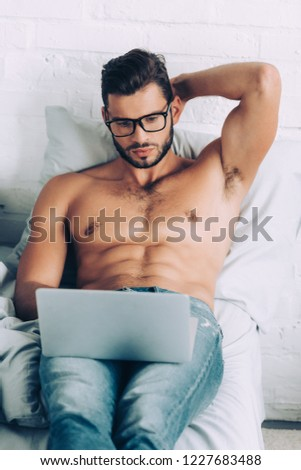 high angle view of shirtless muscular male freelancer in eyeglasses working on laptop in bed at home