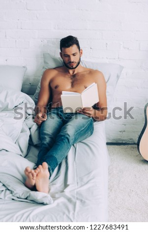 high angle view of shirtless muscular man reading book during morning time in bedroom at home