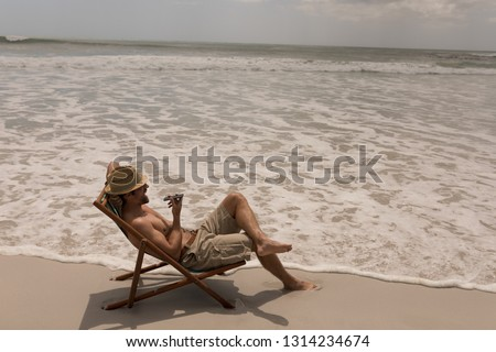 High angle view of shirtless young man with hat relaxing on sun lounger and talking on mobile phone at beach