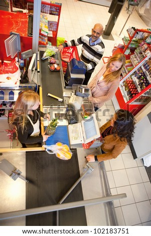 High angle view of shop assistant with customer in supermarket