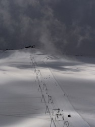 High angle view of skilift by glacier against dark foggy sky