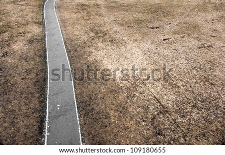 High angle view of small road, walking path or bicycle path in depressing infertile flat landscape