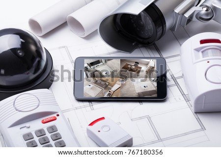 High Angle View Of Smart Home System On Mobilephone With Security Equipment And Blueprint